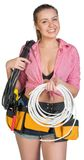Woman in tool belt holding coils of cable Stock Photo