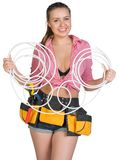 Woman in tool belt holding coils of cable Stock Image