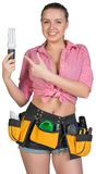 Woman in tool belt holding energy-saving lamp Stock Photo