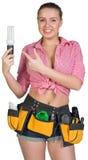 Woman in tool belt holding energy-saving lamp Stock Photo