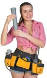 Woman in tool belt holding fitting pipe Royalty Free Stock Photo