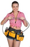 Woman in tool belt holding flexible tap hose Stock Images