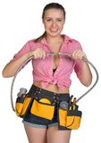 Woman in tool belt holding flexible tap hose Royalty Free Stock Image