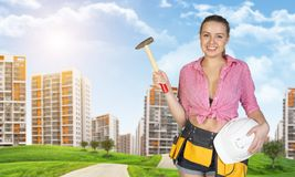 Woman in tool belt holding hammer and helmet Royalty Free Stock Photos