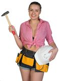 Woman in tool belt holding hard hat and hammer Stock Image