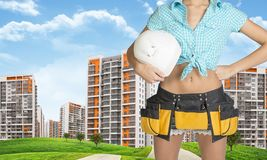 Woman in tool belt holding helmet. Cropped image Royalty Free Stock Photos