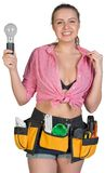 Woman in tool belt holding lamp bulb Stock Images