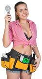 Woman in tool belt holding lamp bulb Stock Image