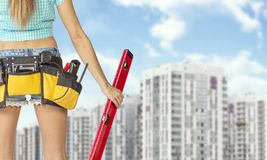 Woman in tool belt holding red building level stock photography