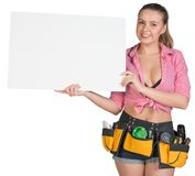 Woman in tool belt showing blank banner Royalty Free Stock Photography