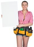 Woman in tool belt showing blank banner Stock Photography