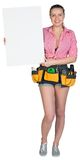Woman in tool belt showing blank banner Royalty Free Stock Image