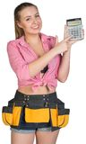 Woman in tool belt showing calculator Royalty Free Stock Photography