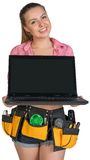 Woman in tool belt showing opened laptop with Stock Images