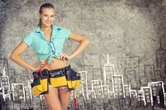 Woman in tool belt standing akimbo against stone Stock Images