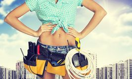 Woman in tool belt standing akimbo. Cropped image. Woman in tool belt with different tools standing akimbo. Cropped image. High-rise residential buildings in Royalty Free Stock Image