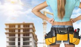 Woman in tool belt standing backwards, akimbo Stock Photos
