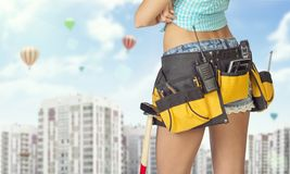 Woman in tool belt standing backwards. Cropped Stock Photo
