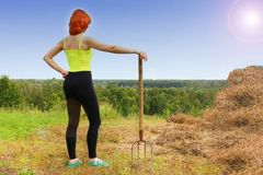 Woman with a tool for harvesting a bevelled row. Woman with a tool for harvesting stock photos