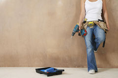 Woman With Toolbelt And Drill Leaning Against Wall. Lowsection of a young woman with toolbelt and drill leaning against wall Royalty Free Stock Image