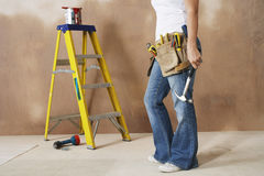 Woman With Toolbelt And Hammer Leaning Against Wall. Lowsection of a woman with toolbelt and hammer leaning against wall Stock Photos