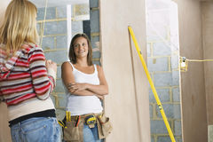 Woman With Toolbelt Talking To Friend. Young women with toolbelt talking to a female friend Stock Photos