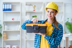 The woman with toolkit in workshop. Woman with toolkit in workshop Stock Photo