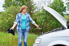 Woman with tools near broken car Royalty Free Stock Images