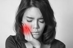 Woman tooth ache. Teen woman pressing her bruised cheek with a painful expression as if she's having a terrible tooth ache Stock Photo