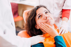 Woman with toothache at dentist Stock Image
