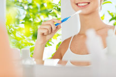 Woman with toothbrush cleaning teeth at bathroom Royalty Free Stock Image