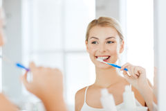 Woman with toothbrush cleaning teeth at bathroom Royalty Free Stock Images