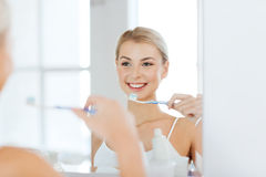Woman with toothbrush cleaning teeth at bathroom Stock Image