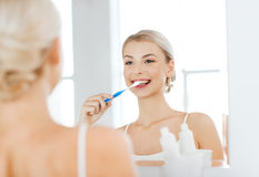 Woman with toothbrush cleaning teeth at bathroom. Health care, dental hygiene, people and beauty concept - smiling young woman with toothbrush cleaning teeth and Stock Photo