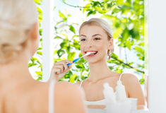 Woman with toothbrush cleaning teeth at bathroom Stock Photo