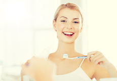 Woman with toothbrush cleaning teeth at bathroom Royalty Free Stock Photography
