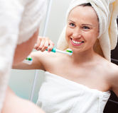 Woman with toothbrush looking at mirror Stock Photo