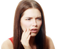 Woman toothpain. Teen woman pressing her bruised cheek with a painful expression as if she's having a terrible tooth ache Royalty Free Stock Photo