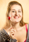 Woman with toothy smile posing with decorative red heart Stock Images
