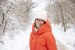 Woman with toothy smile relaxing outdoor in winter. Close-up portrait shot of a happy middle aged woman wearing hat while standing outdoor and enjoy winter Stock Images