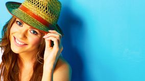 Woman with toothy smile touching hat Royalty Free Stock Image