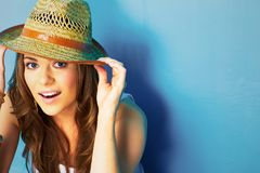 Woman with toothy smile touching hat. With fields Stock Image