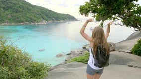 Woman on Top of the Cliff. Young woman standing on cliff`s edge and looking into a wide valley and lagoon. Vacation,adventure and lifestyle concept stock video footage