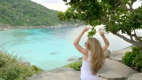 Woman on Top of the Cliff. Young woman standing on cliff`s edge,raising hands up and looking into a wide valley and lagoon. Vacation,adventure and lifestyle stock footage