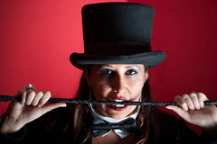 Woman in top hat biting whip. Woman dressed like a circus ringmaster with whip Stock Photos