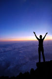 Woman on a top of a mountain. At dawn or sunset Royalty Free Stock Photo