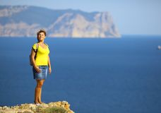 Woman on top of a mountain above the sea. Young woman on top of a mountain above the sea Stock Photos