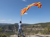 Woman on top of a mountain with Catalonian flag. A Woman on top of a mountain with Catalonian flag Royalty Free Stock Photos