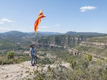 Woman on top of a mountain with Catalonian flag. A Woman on top of a mountain with Catalonian flag Stock Photos