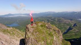 Woman on top of the mountain and falshfeer stock video footage